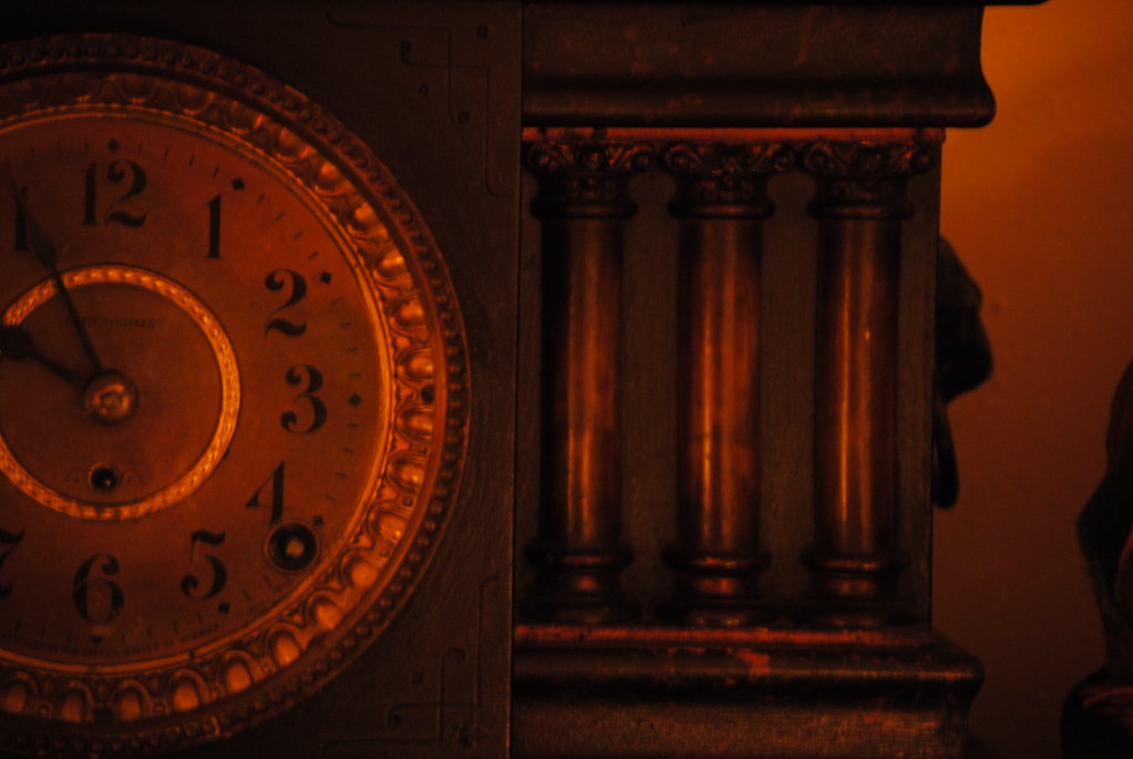Dark image showing half a clock with red lighting